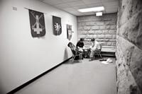 "Privacy is minimal at the clinic housed in Grace Episcopal Church in downtown Madison, but the UW medical students do what they can with the available space. Above, in an exam ""room"" at the end of an L-shaped hall, student Tim Kufahl MDx'11 cares for a patient beneath church banners."