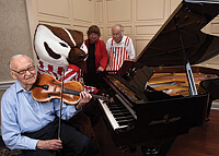 Cultural events are key at the Capitol Lakes retirement center. From left, resident Jim Crow, a UW-Madison emeritus professor of genetics, plays his viola, while Bucky Badger demonstrates his piano skills for residents Janice and Jean-Pierre Golay. Photo: Andy Manis