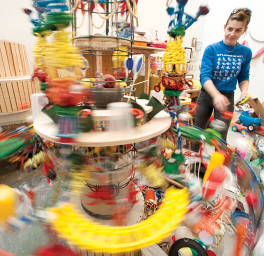 Round and round and round it goes, where it stops, nobody knows. Ginger Lukas MFAx'11 gives her mixed-media project a hearty spin as she contemplates where to place the next element while working in her studio space at the Art Lofts, which opened on campus last year.