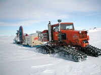 The shot-hole drill (shown during a test near McMurdo Station) carves holes in glaciers in Antarctica. It can drill ice at a rate of six meters per minute, cutting up to twenty holes each day. The drill's bit is made of steel and tungsten, but the key element is compressed air, used to drive the drill, suspend it over the ice, and clear chips out of the hole.
