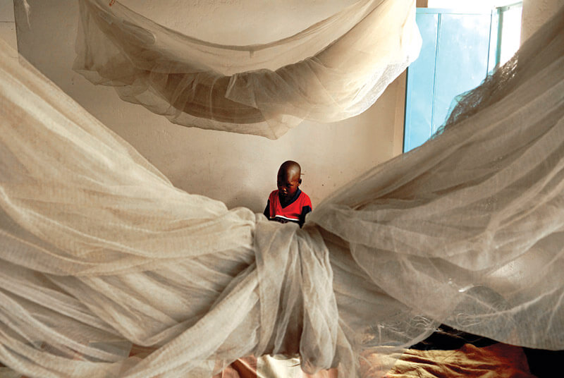 A young refugee in a Darfur hospital sits surrounded by mosquito netting. Suffering from a respiratory infection, he is one of many internally displaced persons afflicted by disease and malnutrition.