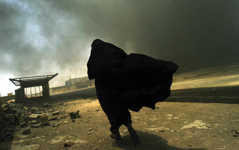 An Iraqi woman searches for her husband as she passes a burning liquid-gas factory in Basra, allegedly  set on fire by looters in the aftermath of the Iraq War.