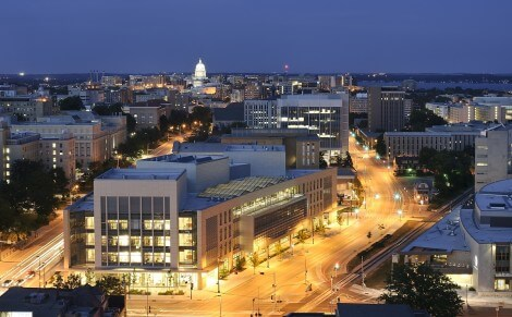 Nighttime falls over the Wisconsin Institutes for Discovery (WID), center; new Union South, at far right; and central University of Wisconsin-Madison campus during a time-exposure photo on July 13, 2011. The 300,000-square-foot WID building houses UW-Madison's public Wisconsin Institute for Discovery and the private Morgridge Institute for Research. On the horizon is the illuminated dome of the Wisconsin State Capitol. The photo was made from the roof of the Engineering Research Building. (Photo by Jeff Miller/UW-Madison)