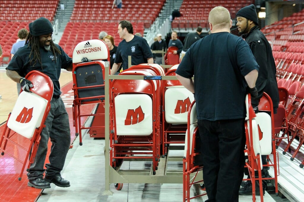 Staff members at the Kohl Center at the University of Wisconsin-Madison work to convert the arena space from a basketball court to an ice hockey rink