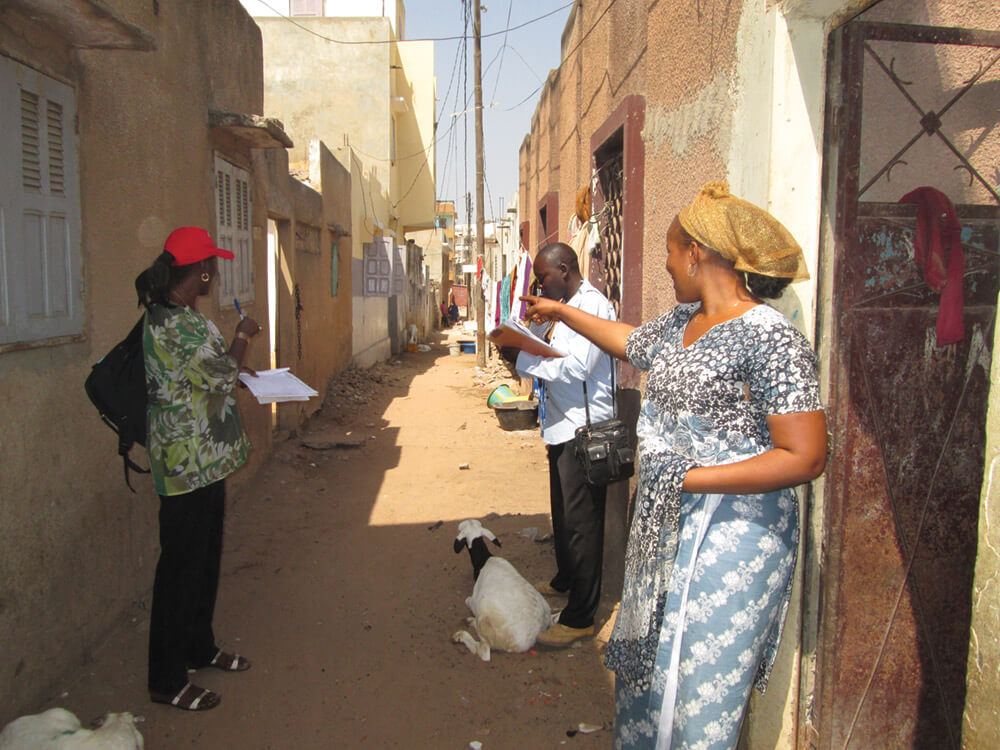 During a sanitation baseline survey to determine what desludging systems residents are currently using, survey-team members  get directions to the next respondent's house from a woman (right) whom they  just finished interviewing. Photo: Ahmadou Kandji.