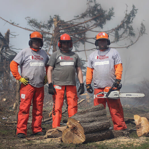 Team Rubicon members with helmuts and chainsaw