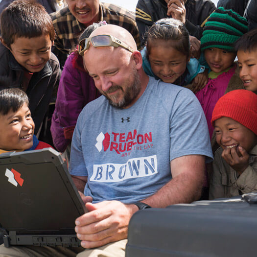 Team Rubicon member surrounded by children