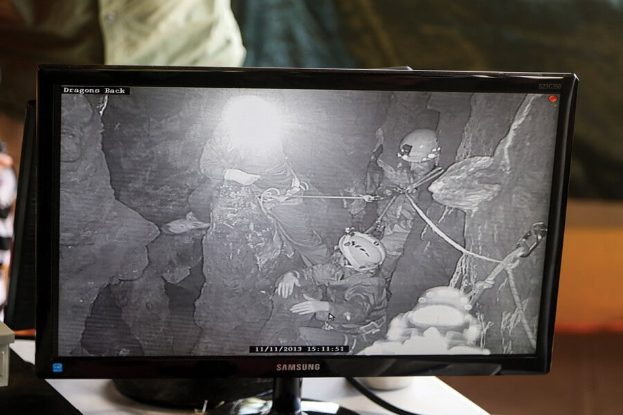 A video screen shows the cavers in the cave.