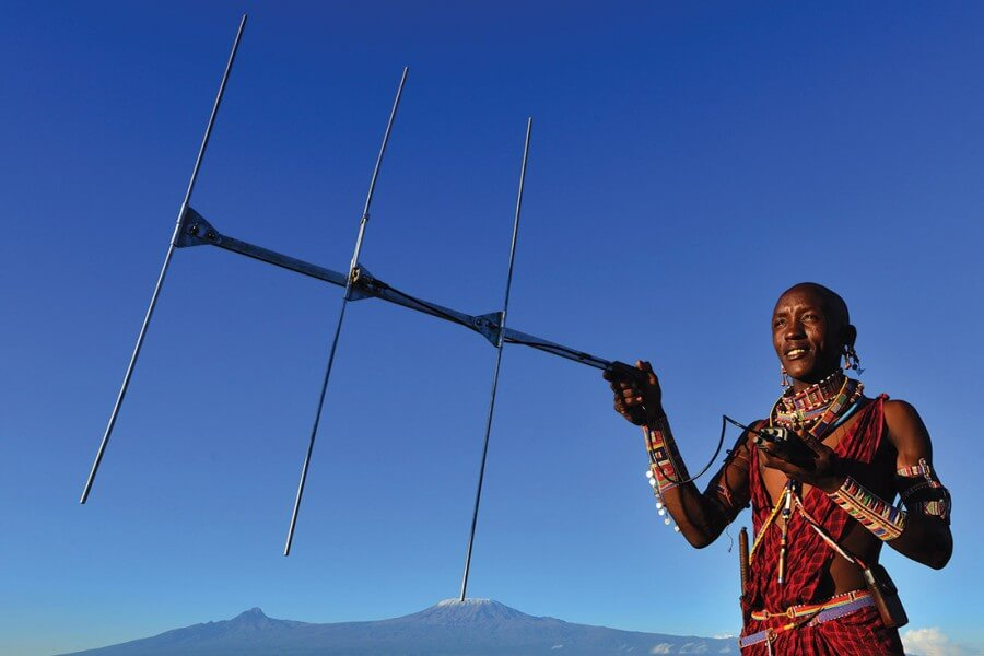 A Masai warrior uses an antenna to track lions