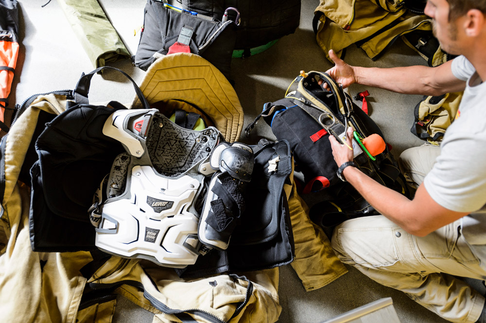 A smokejumper checks his gear at the program's base loft. Almost everything he needs is attached his suit, which includes pieces adapted from motocross and hockey equipment.