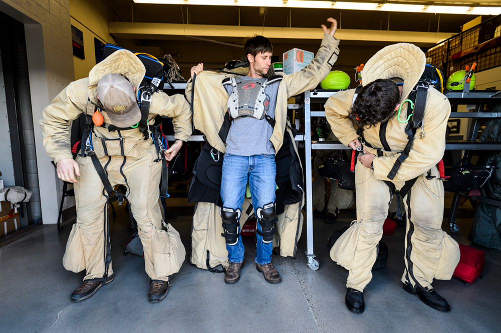 Members suit up in preparation for a practice parachute jump from an airplane.