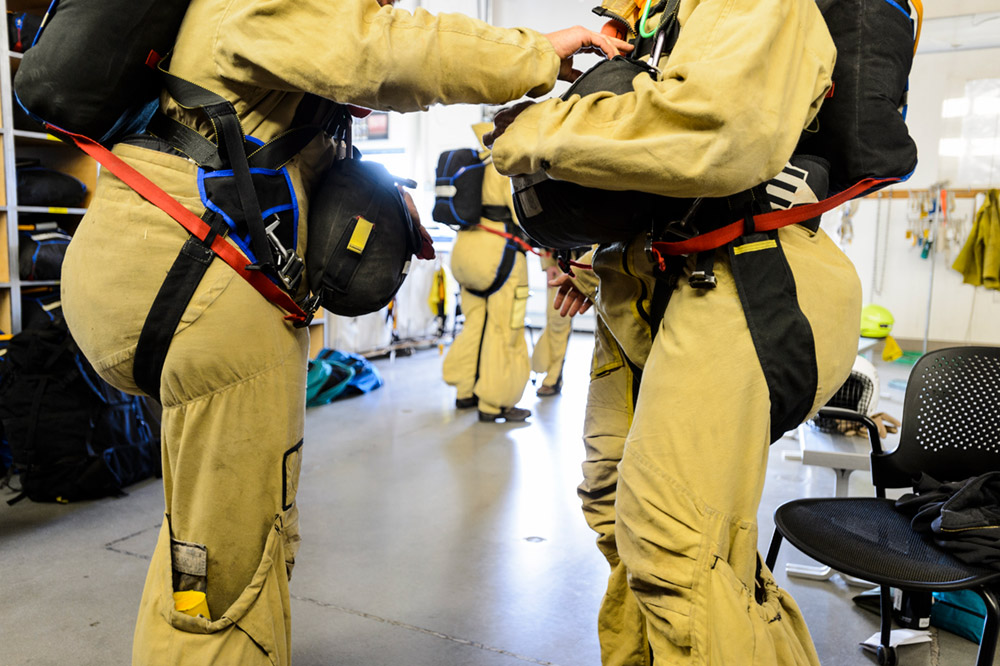"""A pair of smokejumpers do a pre-flight """"buddy check."""" After landing, the jumpsuits turn inside out to become backpacks."""
