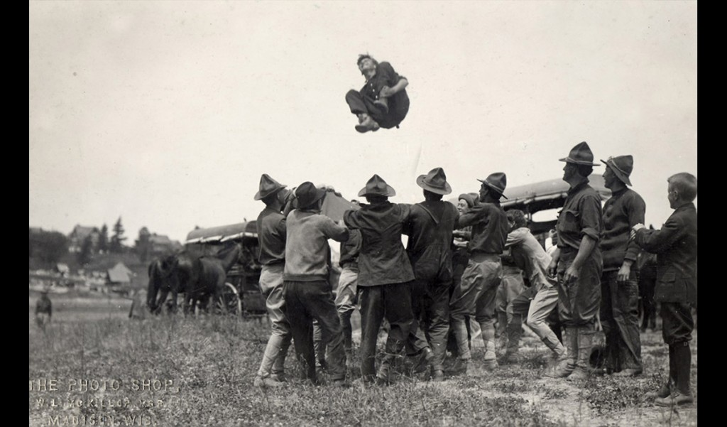 """A group of World War I-era student cadets bounces a new recruit in the air during an initiation ritual. """"The University is reorganized on a war basis and is now in full operation as a military institution so far as the S.A.T.C. students are concerned,"""" acting UW President E.A. Birge said of the Student Army Training Corps in a talk to alumni in Chicago in 1918. UW Archives S05412"""