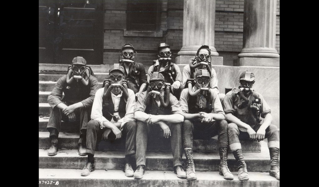 """A group of student soldiers demonstrates gas masks. World War I was the first war to involve poison gas and UW researchers studied chemical warfare in the basement of Science Hall —an effort that was known as """"the gas project."""" In February 1918, the Wisconsin Alumni Magazine reported that UW scientists """"have been working night and day to test the effects of gases and to devise automatic apparatus for detection of gases."""" UW Archives S05411"""