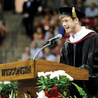 Anders Holm in cap and gown stands at podium and speaks into microphone.