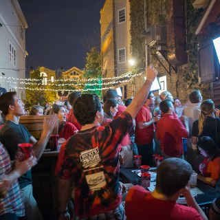 Crowd of people cheering while watching a TV on an outdoor deck at night.