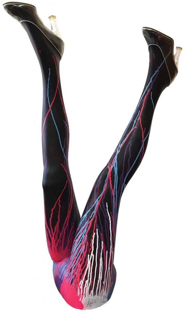Upside-down pair of black mannequin legs streaked with colorful paint and wearing high healed shoes.