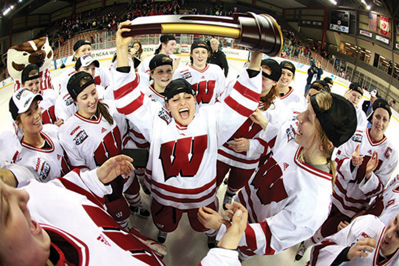 UW Women's Hockey team gather together on rink, smiling as one member holds trophy over her head triumphantly.