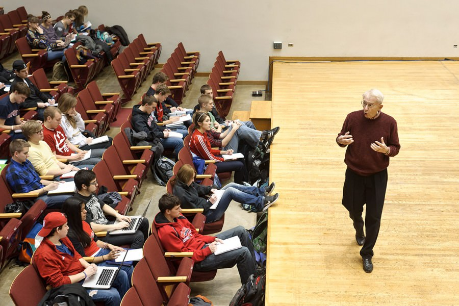 UW Marching Band director, Mike Leckrone, talks in front of a group of students in lecture hall.