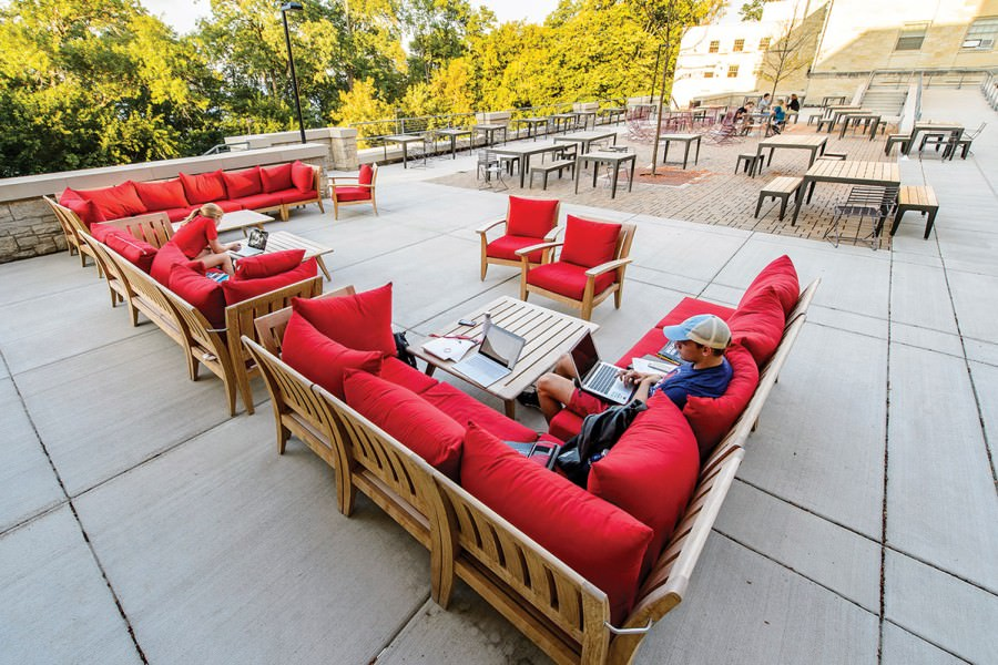 Two students work on laptops while seated on red cushioned outdoor furniture on patio