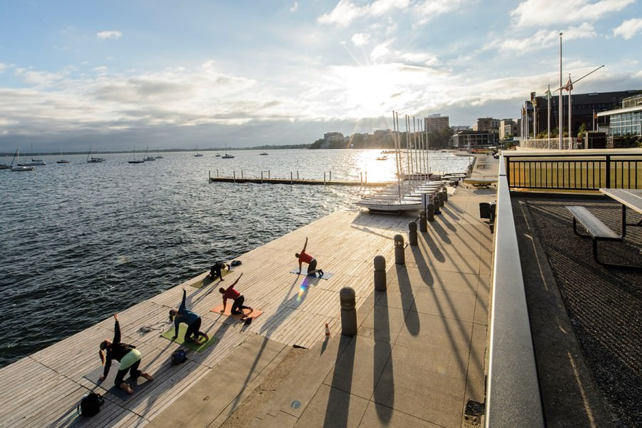 People practicing yoga on wooden deck on the shore of Lake Mendota during sunrise