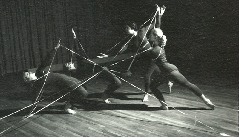 Black and white photo of four women wearing black unitards doing a modern dance routine.