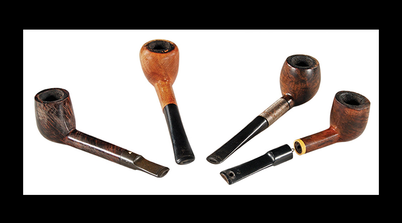 Four carved wooden pipes.