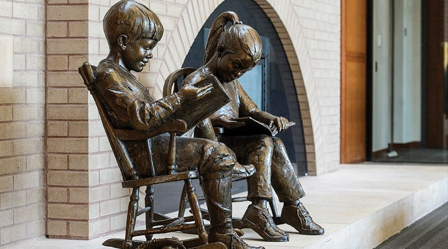 Side-by-side bronze statues of boy and girl sitting in chairs, reading books.