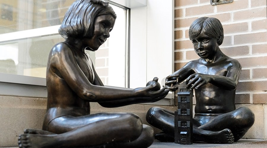 Side-by-side bronze statues, both seated on ground, of a girl holding a bird and a boy playing with Lego bricks.