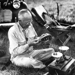Black and white photograph of Aldo Leopold sitting in grass working with scientific equipment.