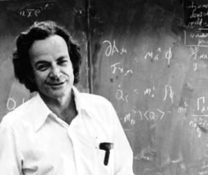 Black and white photo of Richard Feynman standing in front of chalkboard.