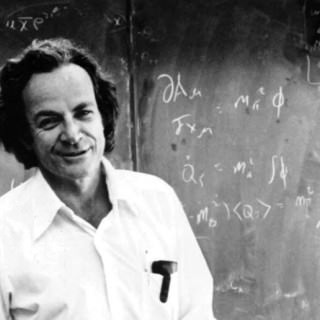 Black and white photo of Richard Feynman in front of chalkboard.