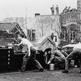 Black and white photo of four male students throwing eggs off of a rooftop.