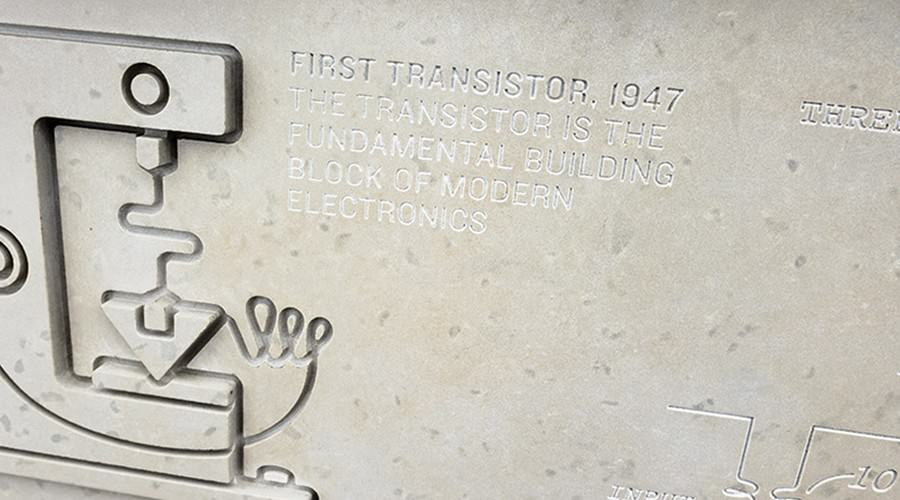 "Stone panel with illustration of transistor carved into side along with text ""First transistor."""