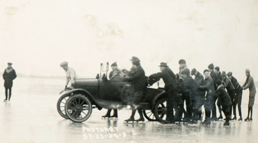 Black and white photo of people pushing car on Lake Mendota.