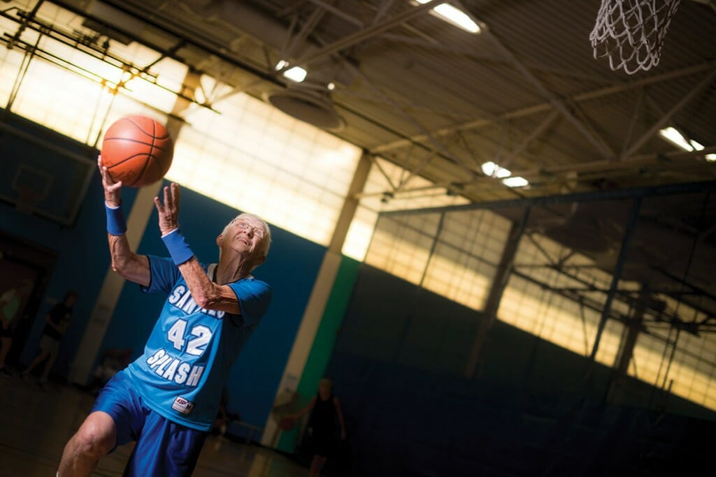 Jo Ann Heckroth Jansen in basketball court wearing jersey and holding basketball approaches basket for a layup