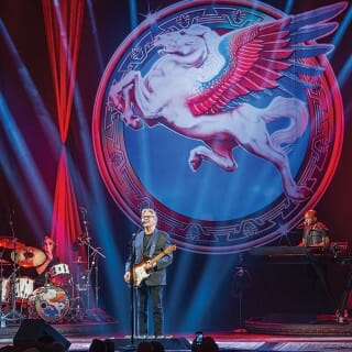 The Steve Miller band performs onstage in front of colorful backdrop.