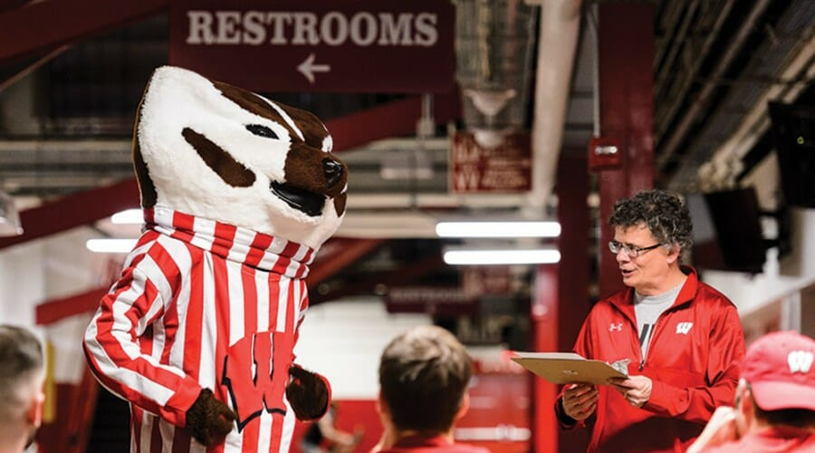 Man with clipboard and Bucky Badger mascot stand in front of group of people.