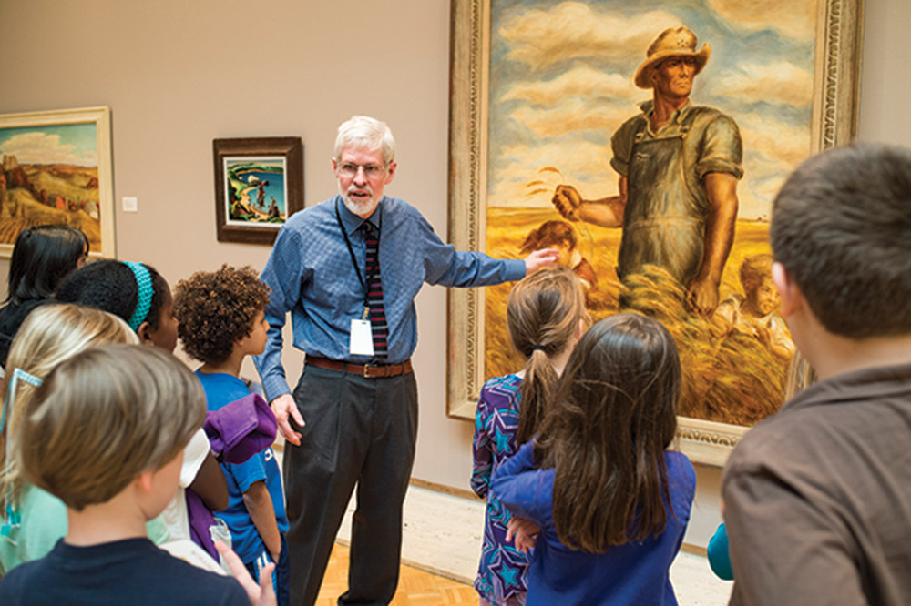 Docent gestures toward large painting in front of group of young children at the Chazen Museum of Art