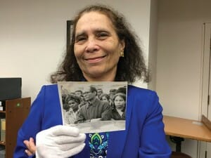 Daphne Barbee-Wooten holding up black and white photo of Lloyd Barbee.