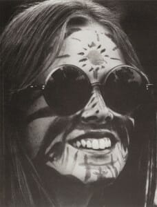 Black and white closeup of woman's face wearing sunglasses and face paint.