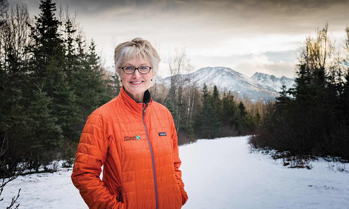 Fran Ulmer stands outdoors against a snowy wooded backdrop with mountains in the distance.