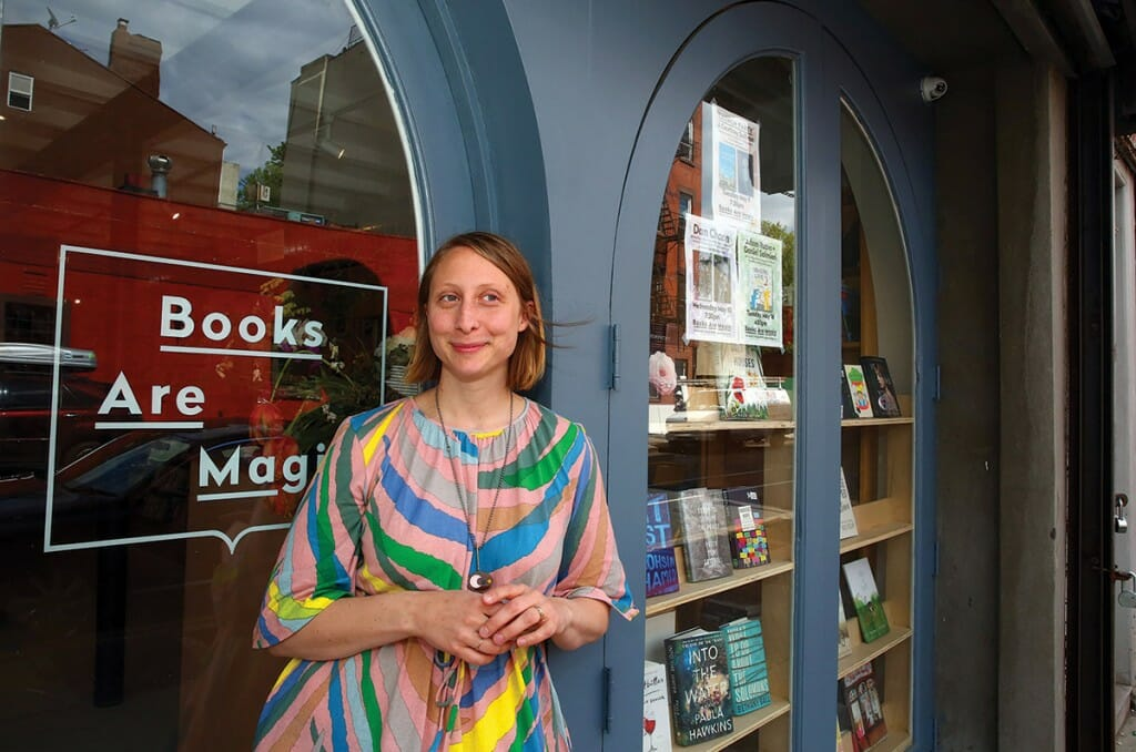"Emma Straub stands in front of storefront sign that reads ""Books Are Magic."""