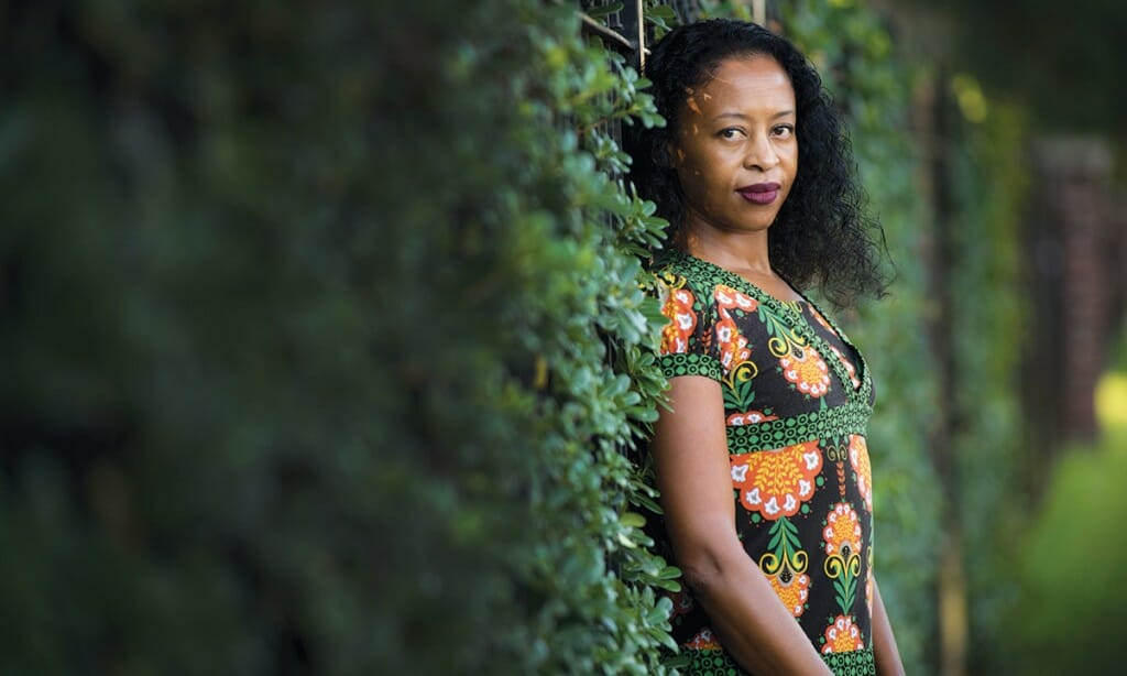 Portrait of Ladee Hubbard standing against vine-covered wall