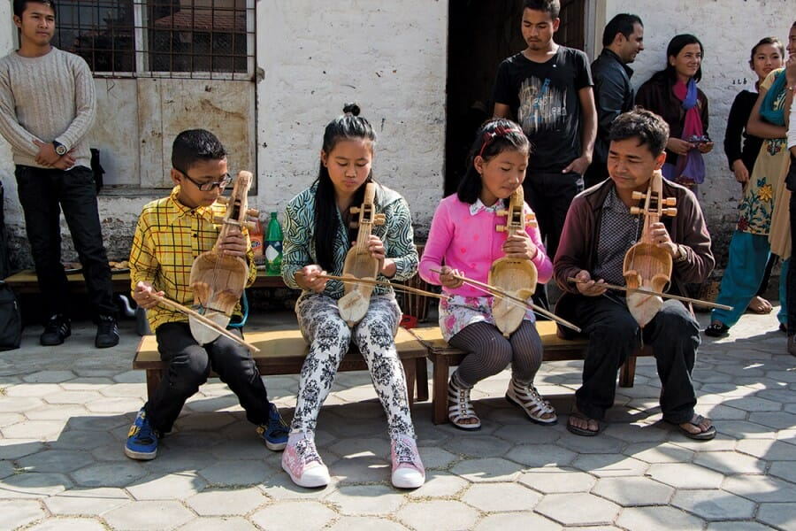 Four children seated on a bench play stringed instruments.