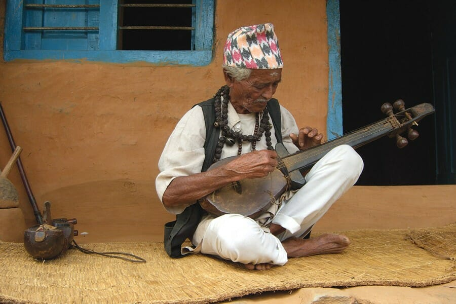 A Nepali man, seated, plays a stringed instrument.