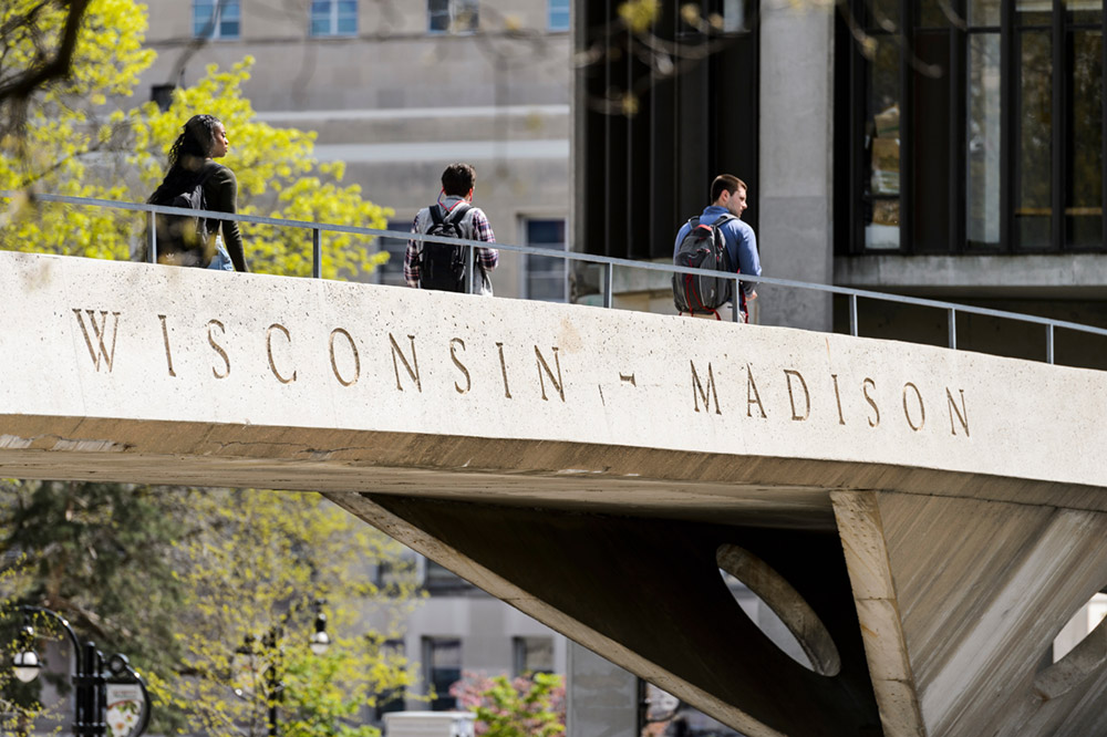 "Students walk along pedestrian bridge with words ""Wisconsin-Madison"" engraved on side."