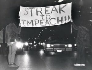 "Nighttime black and white photo of two people blocking traffic while holding either end of large sign that reads ""Streak to impeach!!"""
