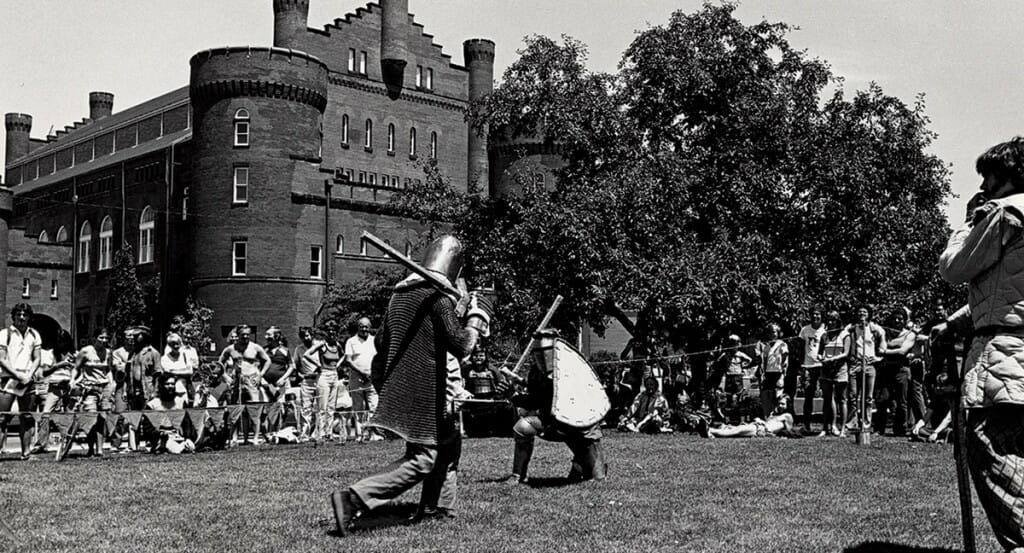 Black and white photograph of two people in medieval armor sparring as crowd watches outdoors.