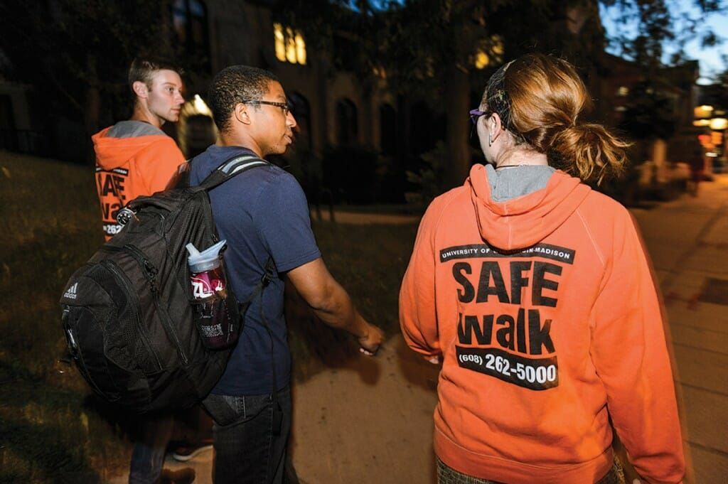 "Two students wearing orange sweatshirts with ""SafeWalk"" logo escort a third student along a dark street"